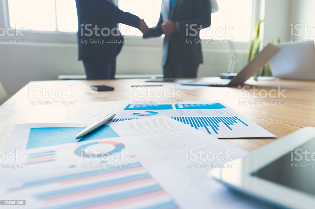 Two businessmen shaking hands with paperwork. stock photo