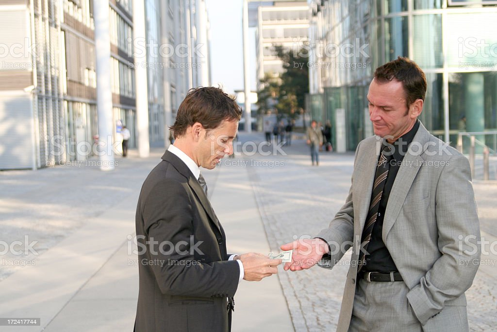 Two businessmen standing on a street discussing business stock photo