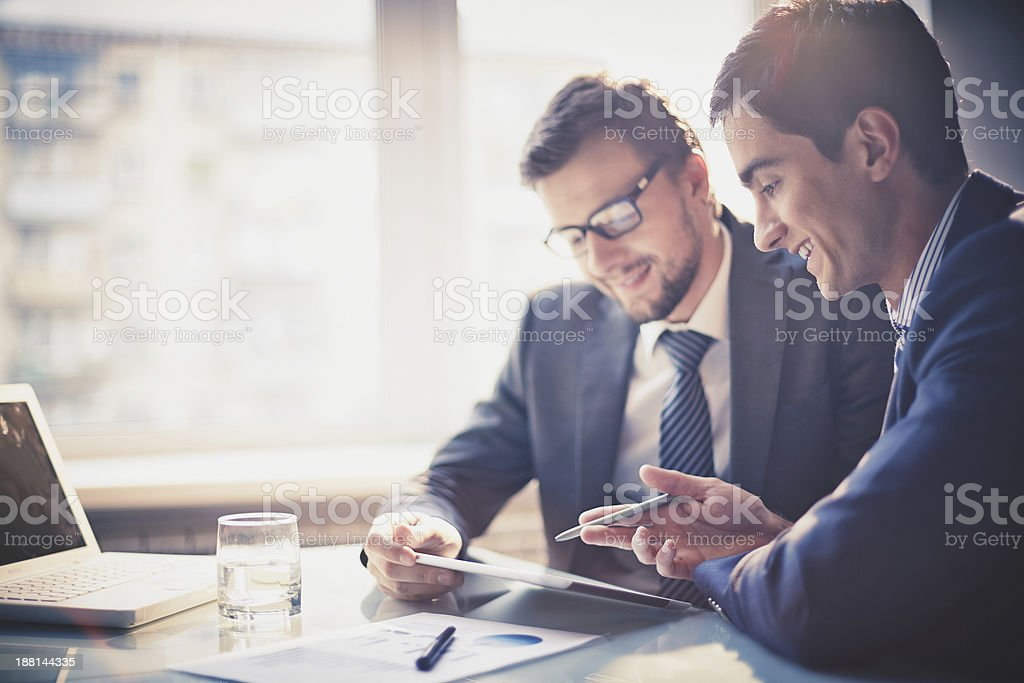Two businessmen talking while looking at notes stock photo