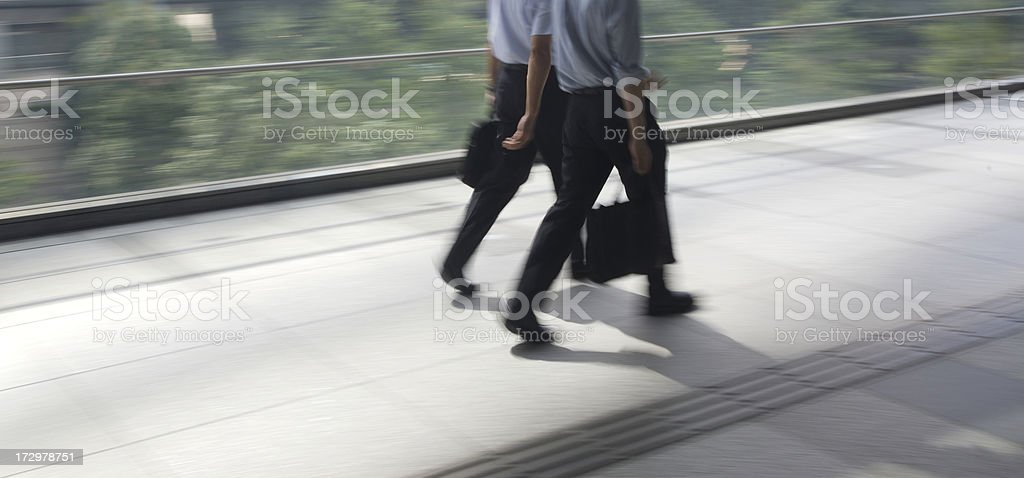 Two businessmen walking and talking royalty-free stock photo