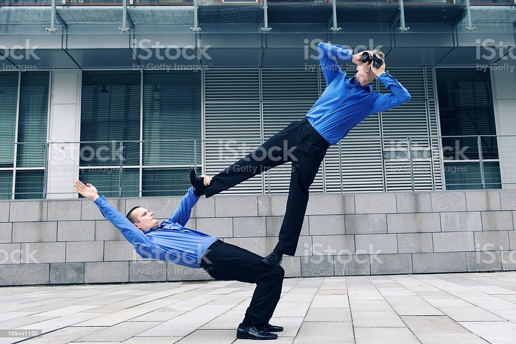 Two businessmen with acrobatic skills work together stock photo