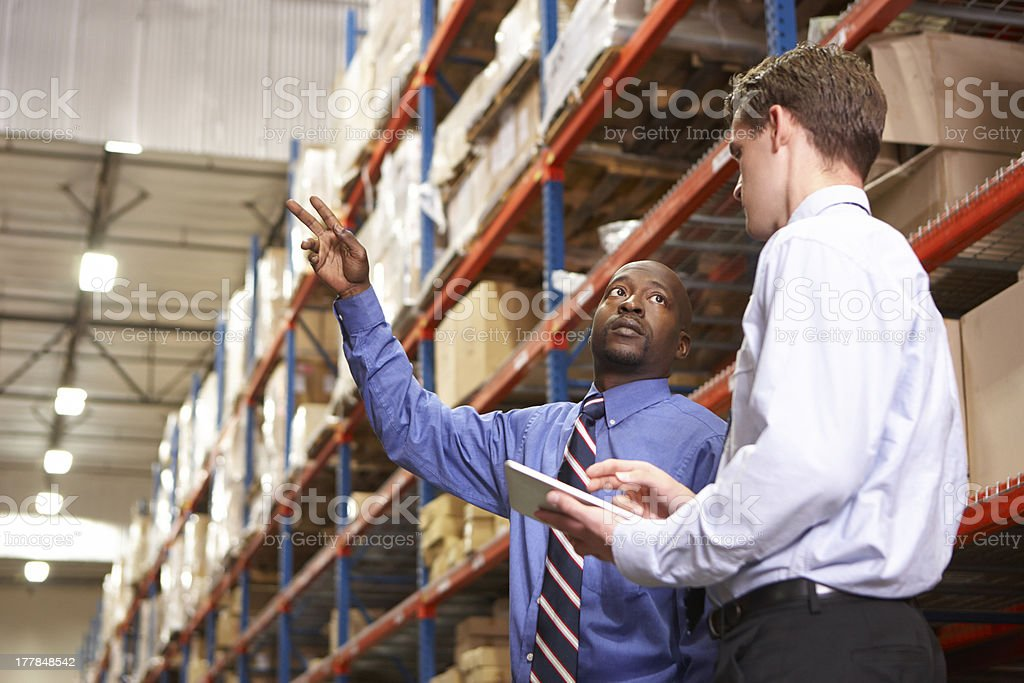 Two Businessmen With Digital Tablet In Warehouse stock photo