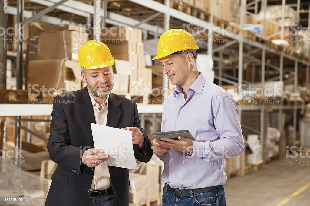 Two businessmen working in warehouse royalty-free stock photo