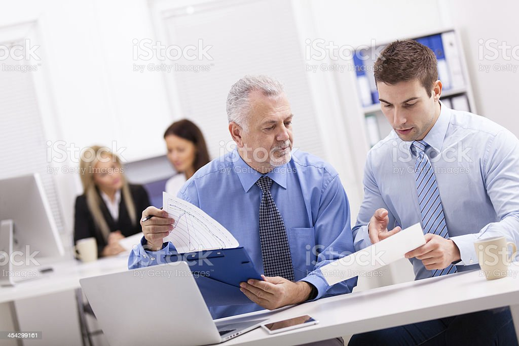 Two businessmen working together analyzing data. stock photo