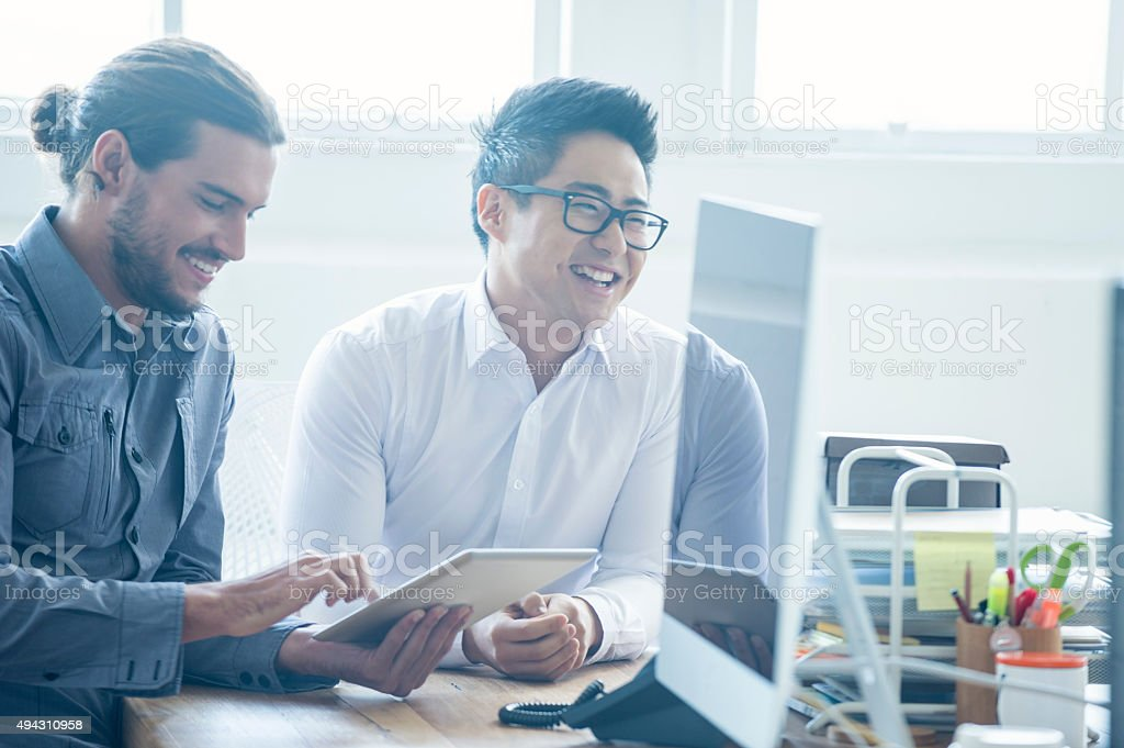 Two businessmen working with a digital tablet. stock photo