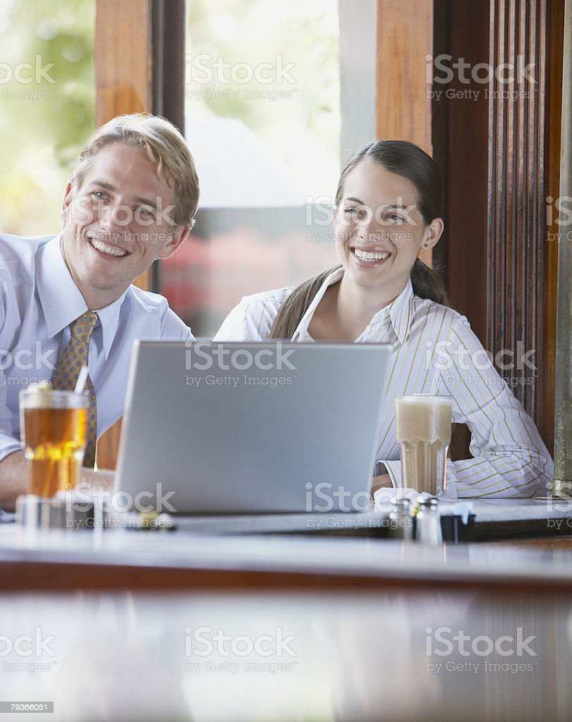 Two businesspeople at a bar with a laptop royalty-free stock photo