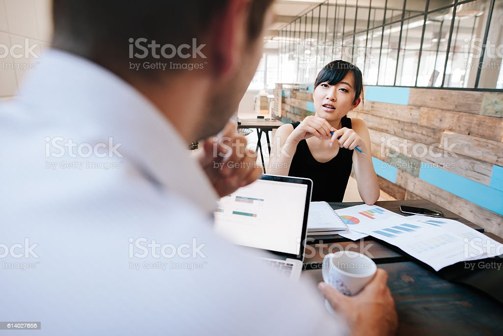 Two businesspeople discussing work in office stock photo