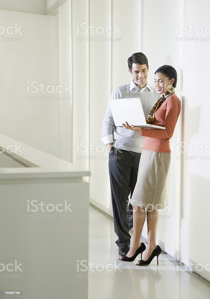 Two businesspeople in an office looking at a laptop royalty-free stock photo
