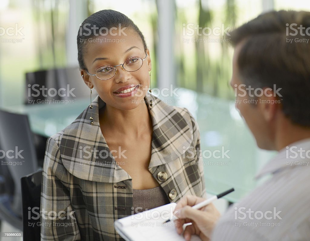 Two businesspeople in boardroom with notepad stock photo