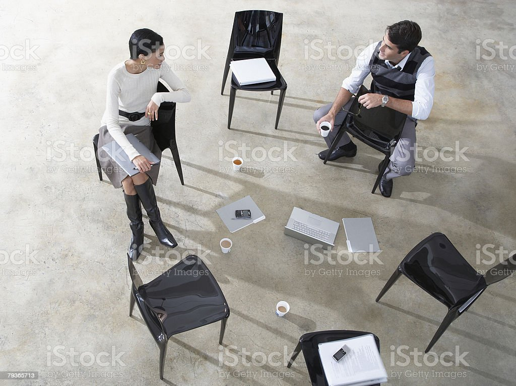 Two businesspeople indoors with laptop and folders stock photo