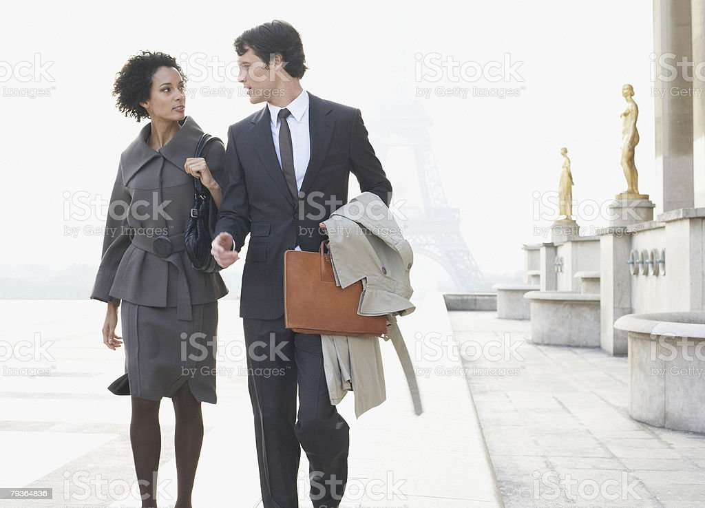 Two businesspeople outdoors walking by building near Eiffel Tower royalty-free stock photo