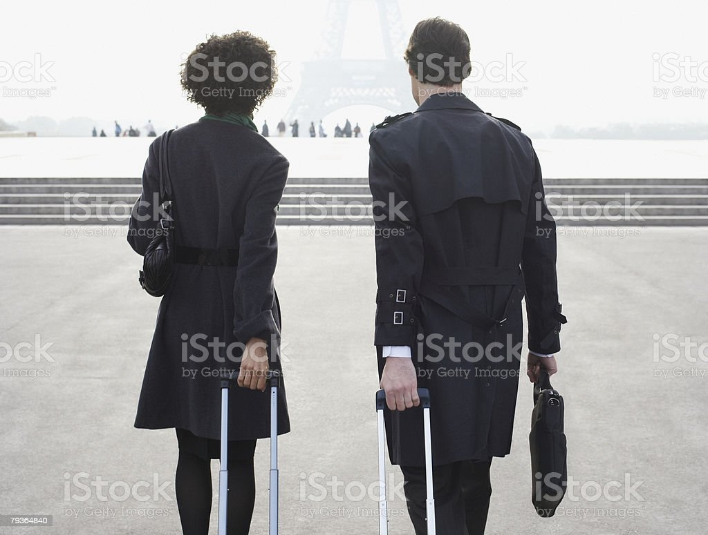 Two businesspeople outdoors with luggage by Eiffel Tower royalty-free stock photo