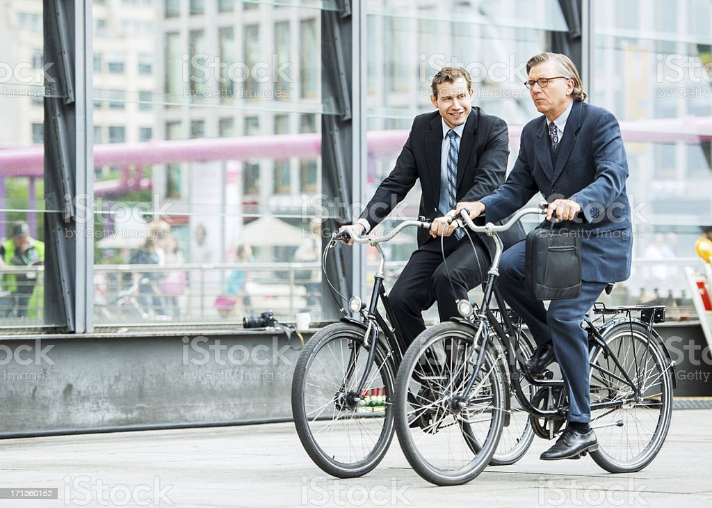 Two businesspeople riding bicycles. royalty-free stock photo