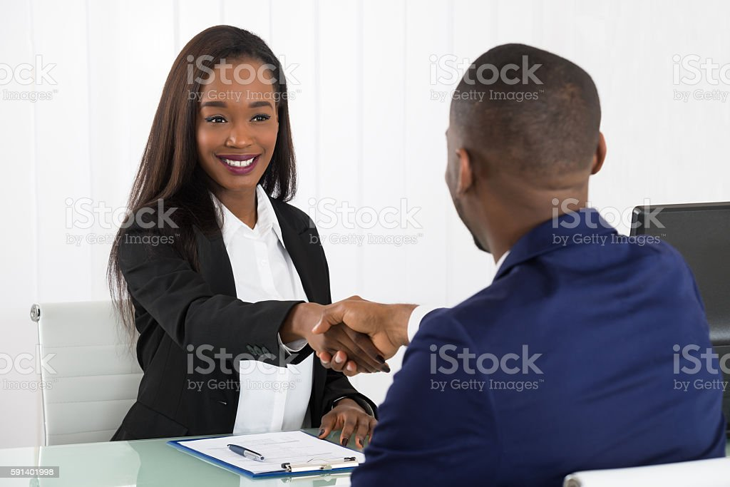 Two Businesspeople Shaking Hands At Office stock photo