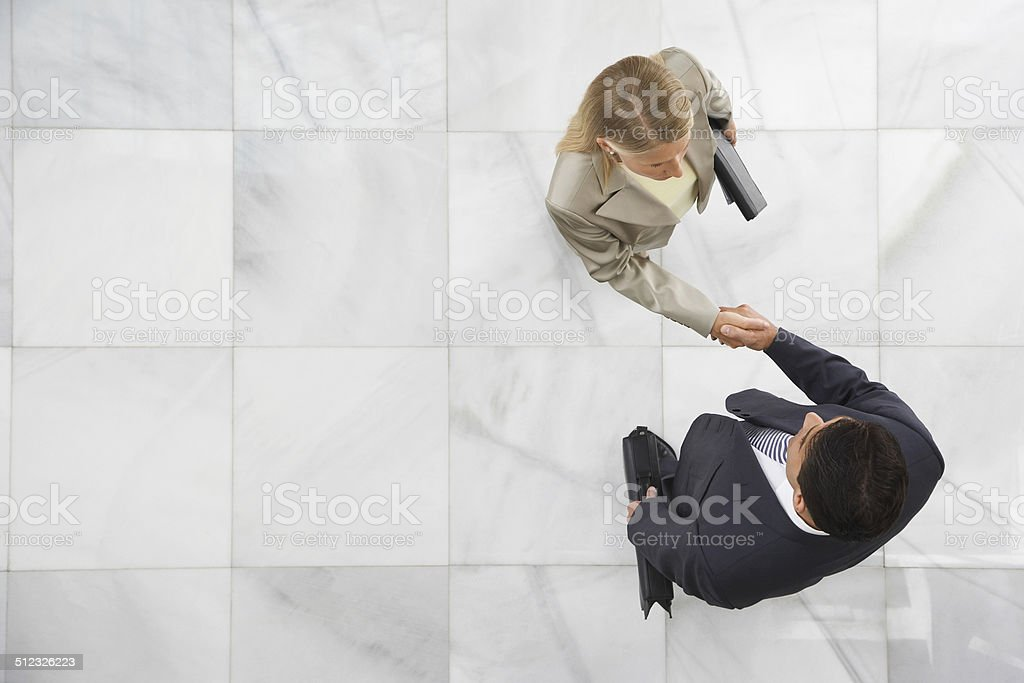 Two Businesspeople Shaking Hands In Lobby stock photo