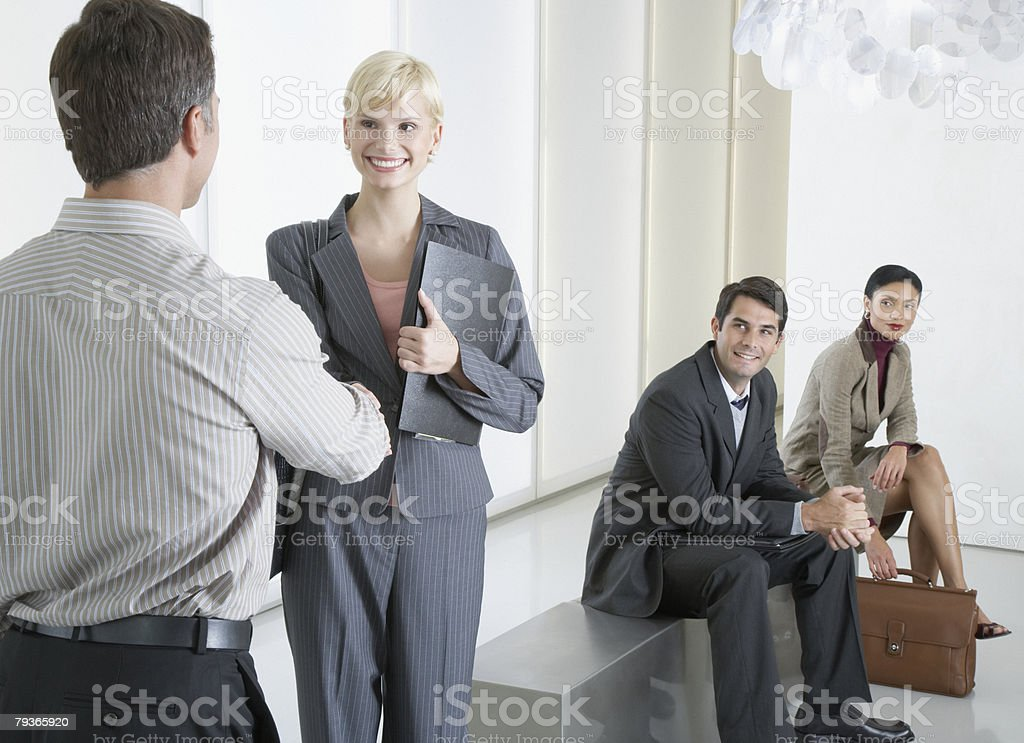 Two businesspeople shaking hands in office lobby with two businesspeople watching royalty-free stock photo
