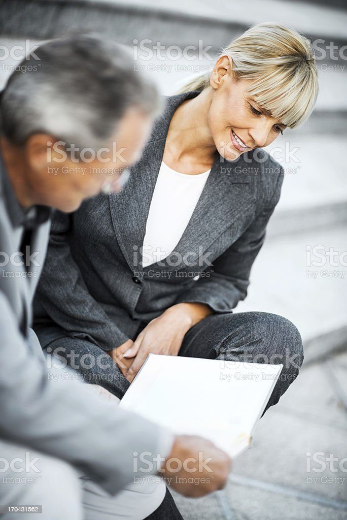 Two businesspeople sitting on stairs and looking at notebook. royalty-free stock photo