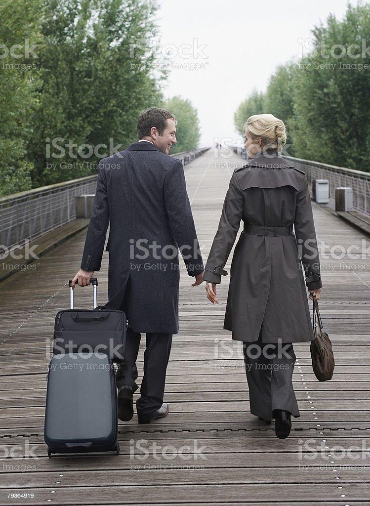 Two businesspeople walking on bridge with luggage royalty-free stock photo