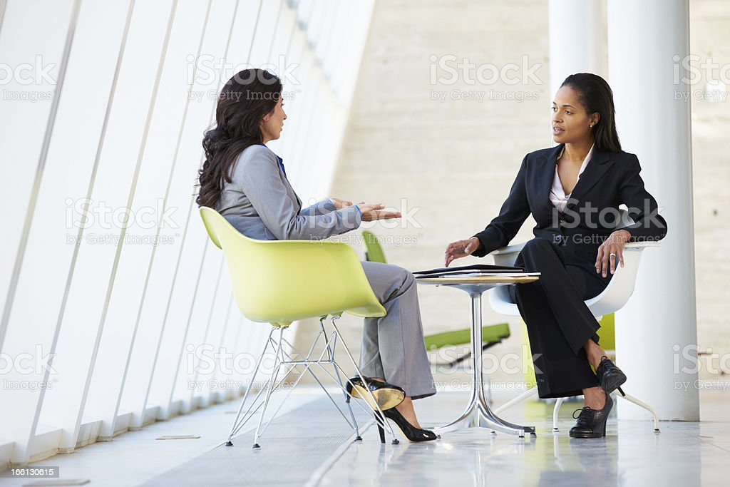 Two businesswoman at a table in modern office stock photo