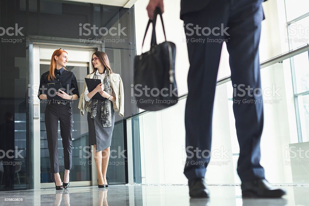 Two businesswoman exiting the elevator and walking stock photo
