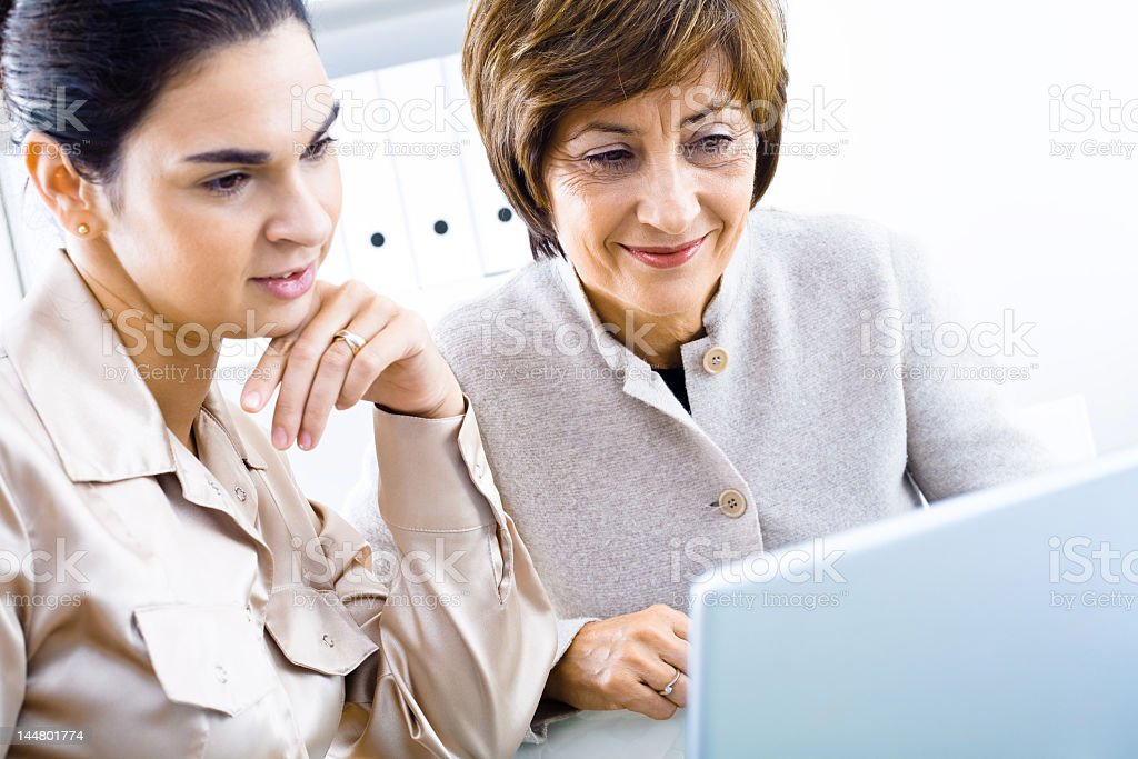 Two businesswoman looking at blue laptop while at work stock photo