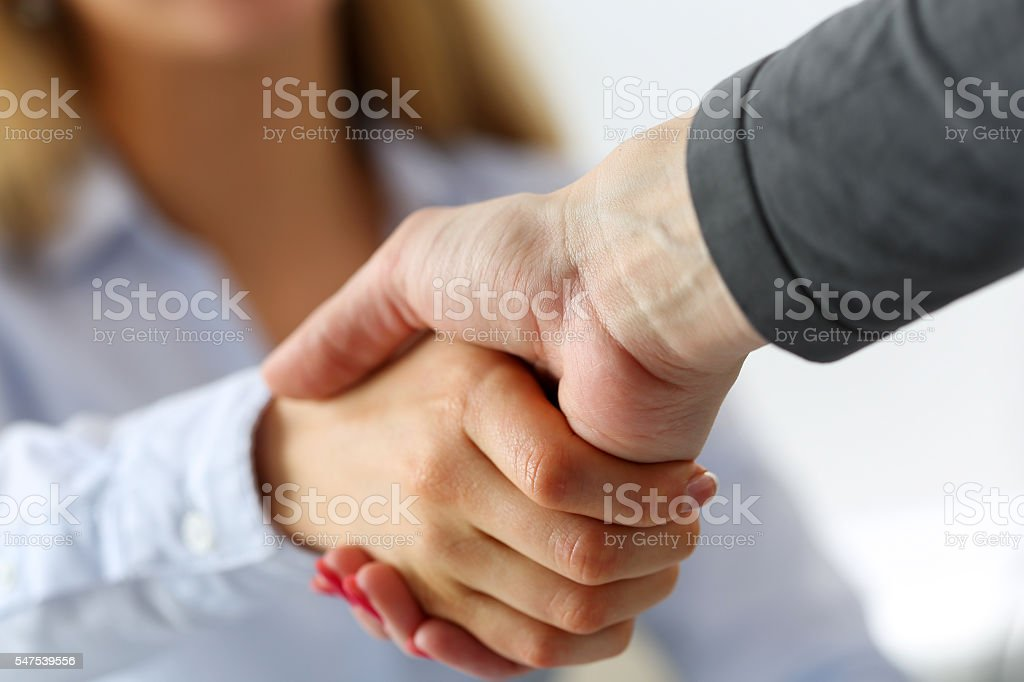 Two businesswoman shake hands as hello stock photo
