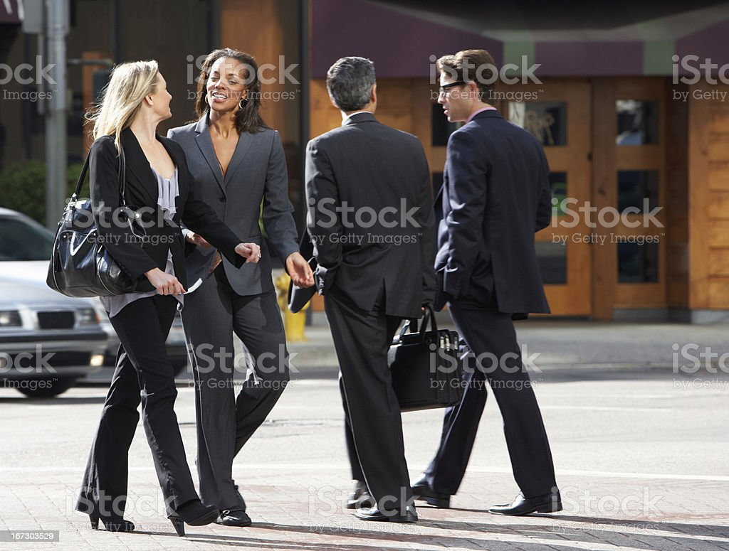 Two Businesswomen Chatting Whilst Crossing Street royalty-free stock photo