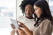 Two businesswomen holding digital tablet, Hispanic woman pointing