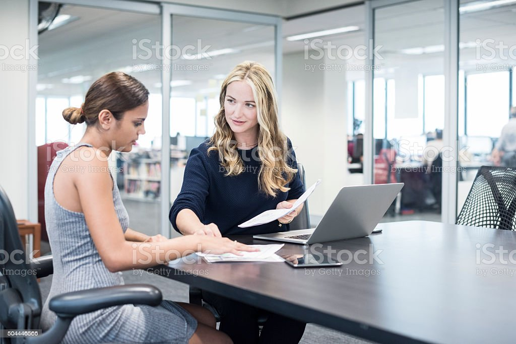 Two businesswomen in modern office looking at documents stock photo