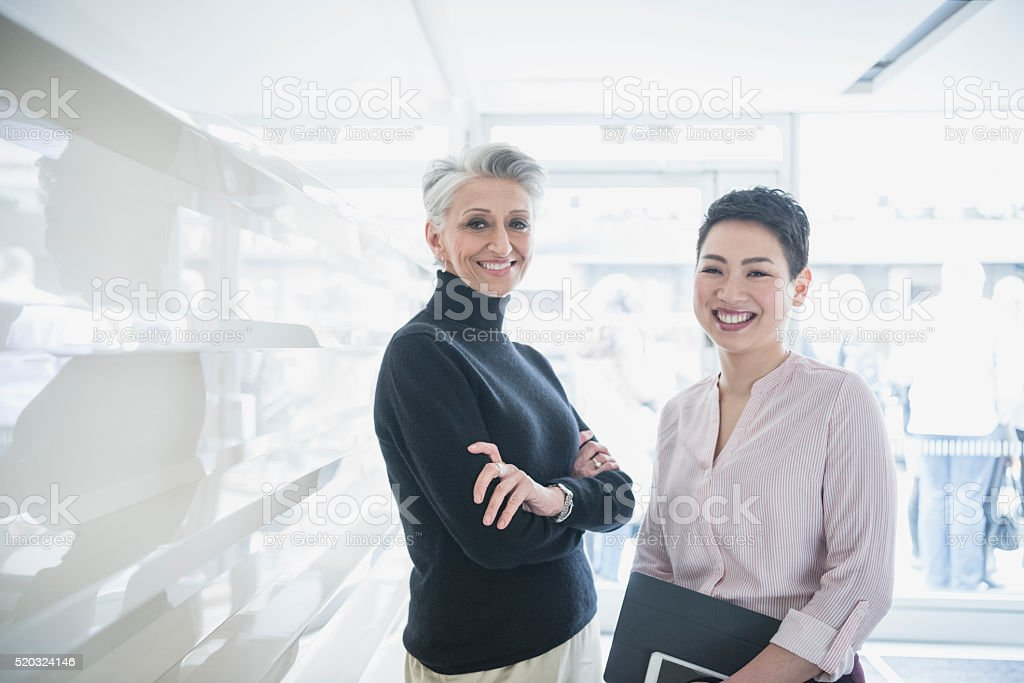 Two businesswomen in modern office, smiling stock photo