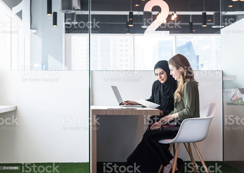 Two businesswomen in office cubicle, Dubai, UAE stock photo