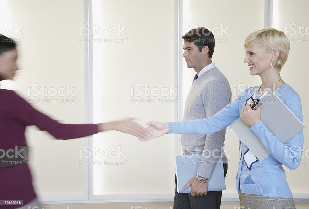 Two businesswomen in office shaking hands with businessman nearby royalty-free stock photo