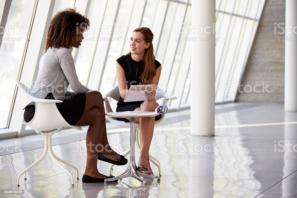 Two Businesswomen Meeting In Reception Of Modern Office stock photo