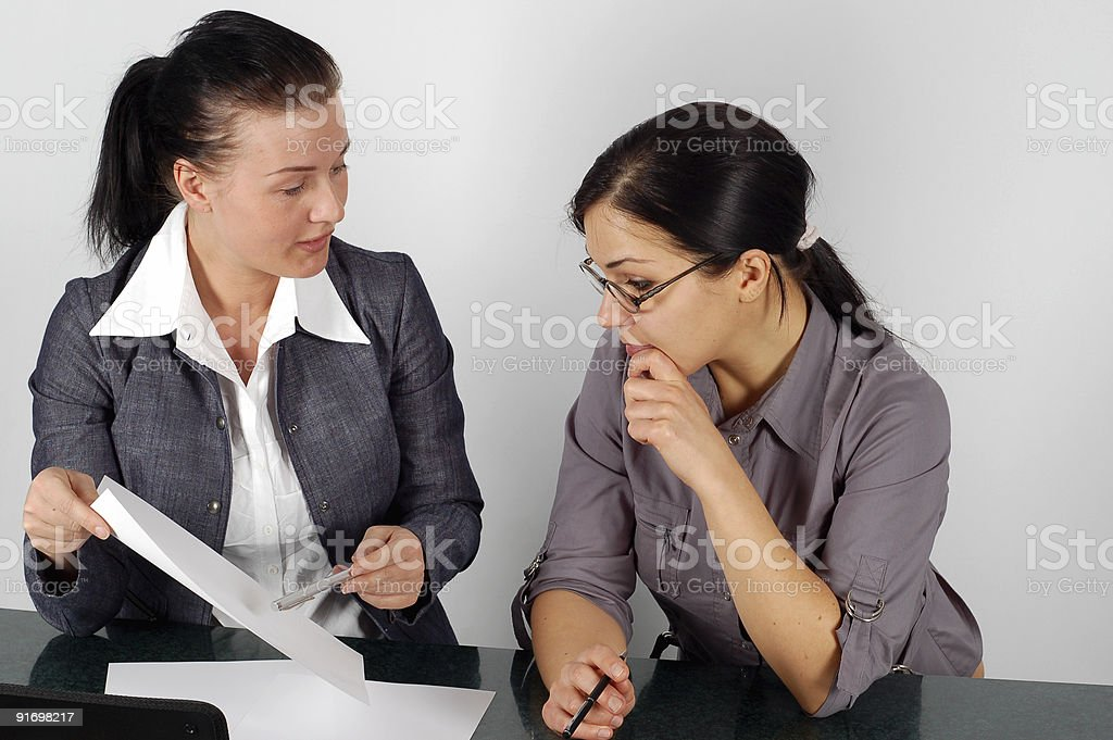 Two businesswomen reviewing a report working as a team royalty-free stock photo
