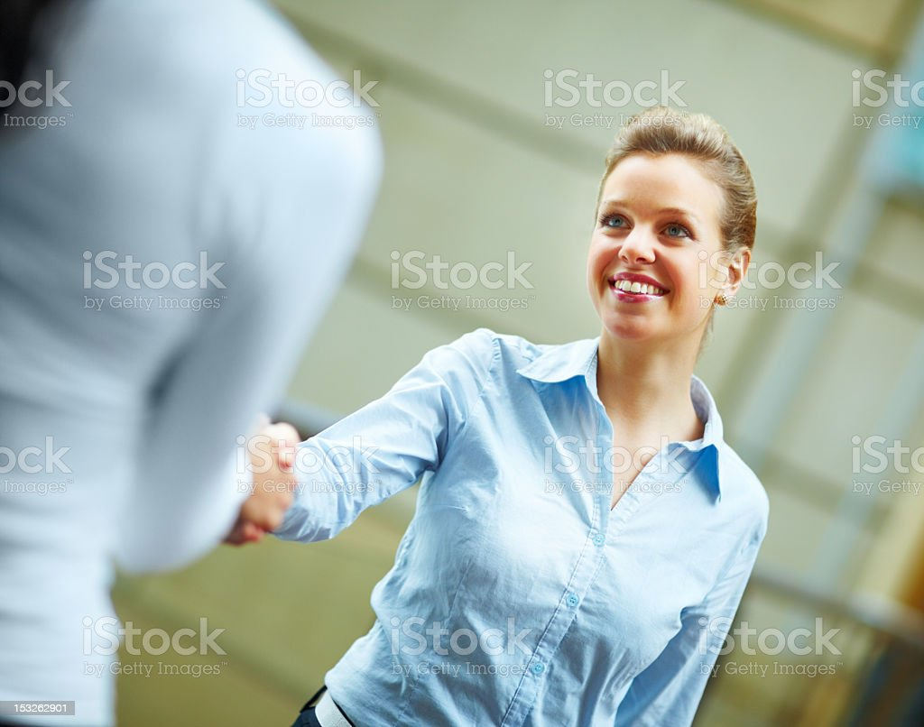 Two businesswomen shaking hands and smiling royalty-free stock photo