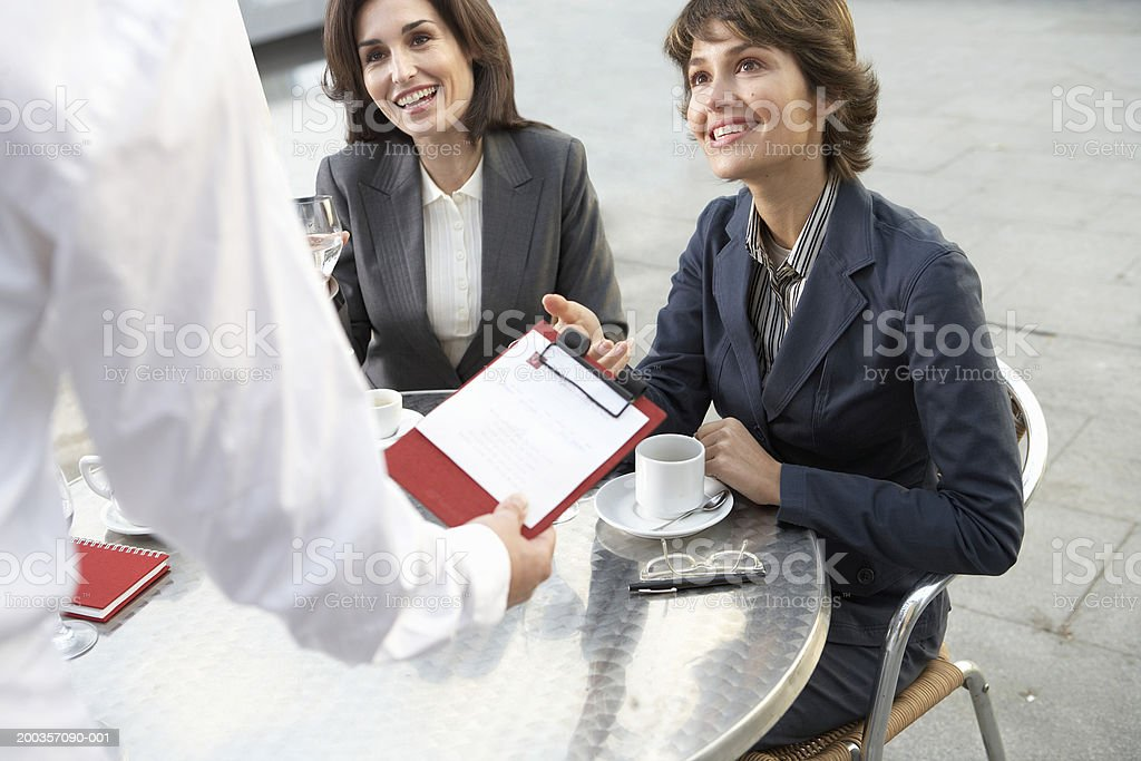 Two businesswomen sitting at table, man passing them clipboard royalty-free stock photo