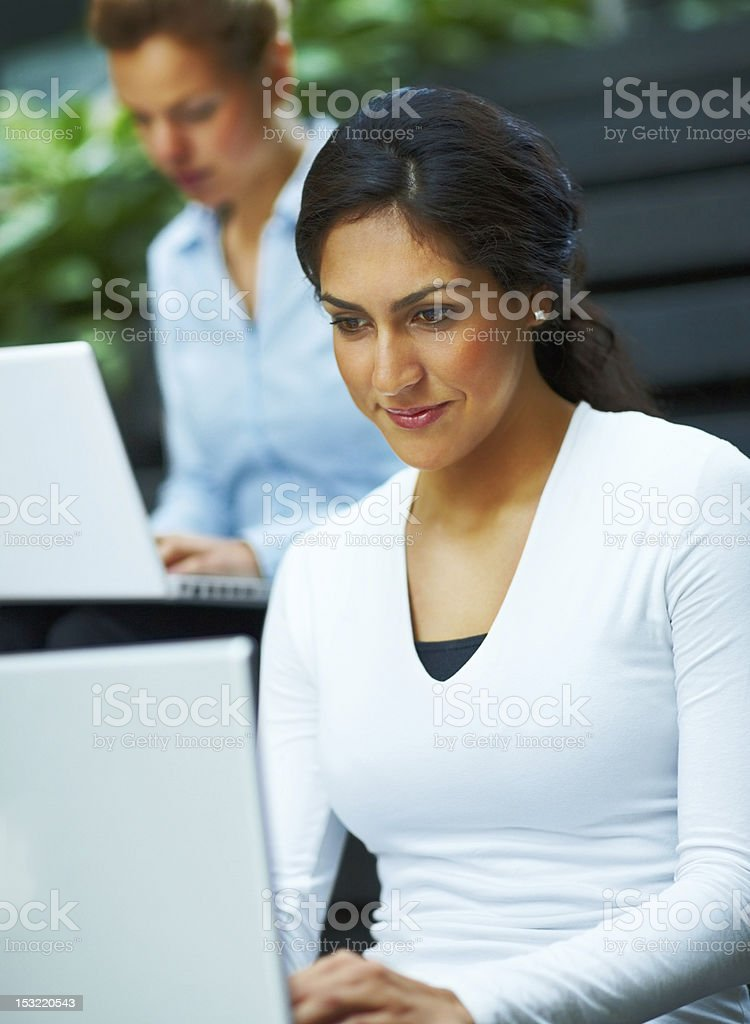 Two businesswomen sitting on the stairs and using laptops royalty-free stock photo