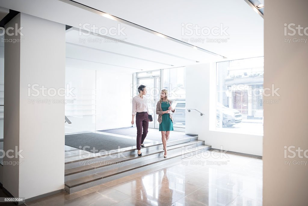 Two businesswomen walking down steps in modern office stock photo