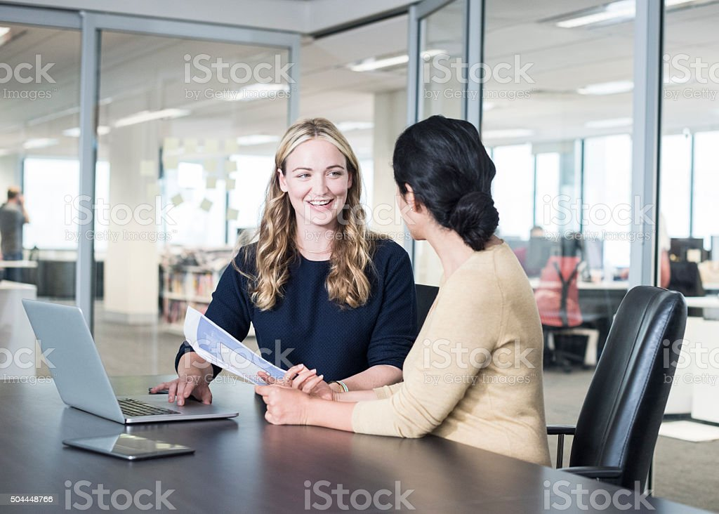 Two businesswomen with documents and laptop in modern office stock photo