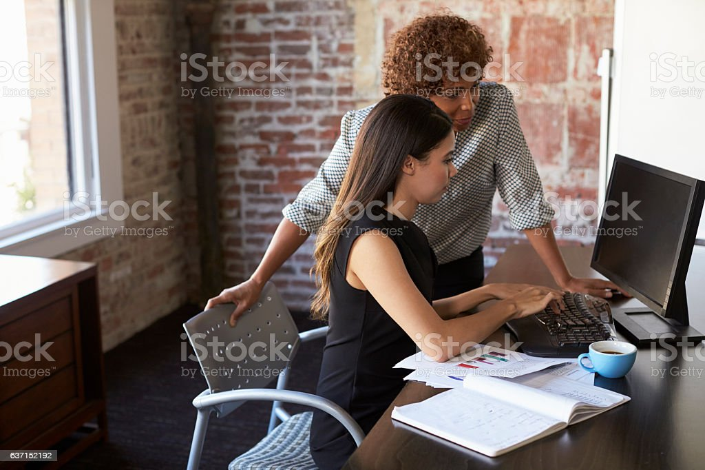 Two Businesswomen Working On Computer In Office stock photo