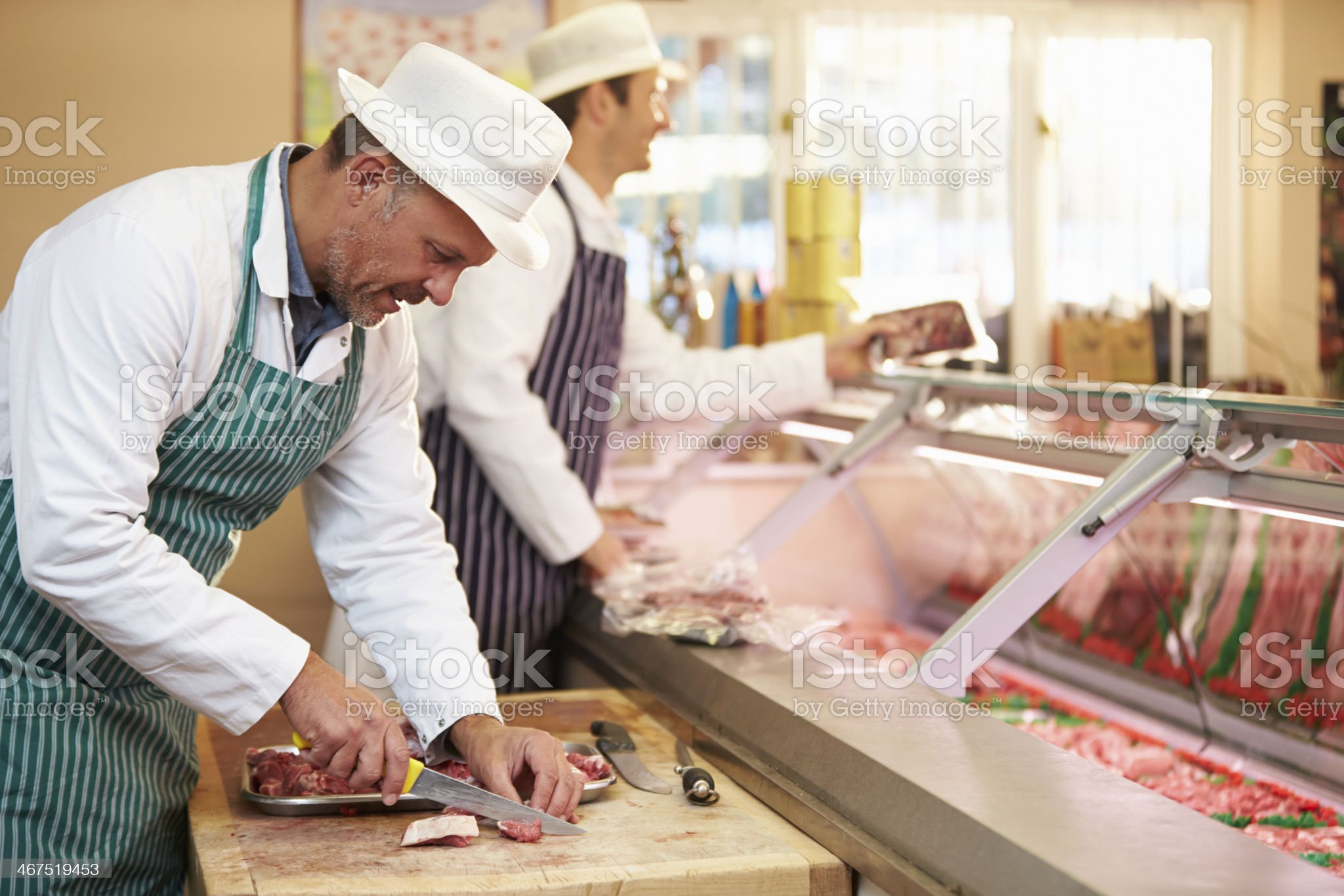 Two butchers in striped aprons at work royalty-free stock photo
