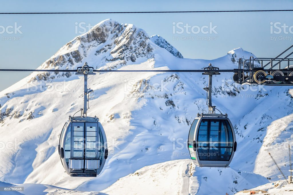 Two cableway ski lift cabins on snowy mountain background stock photo