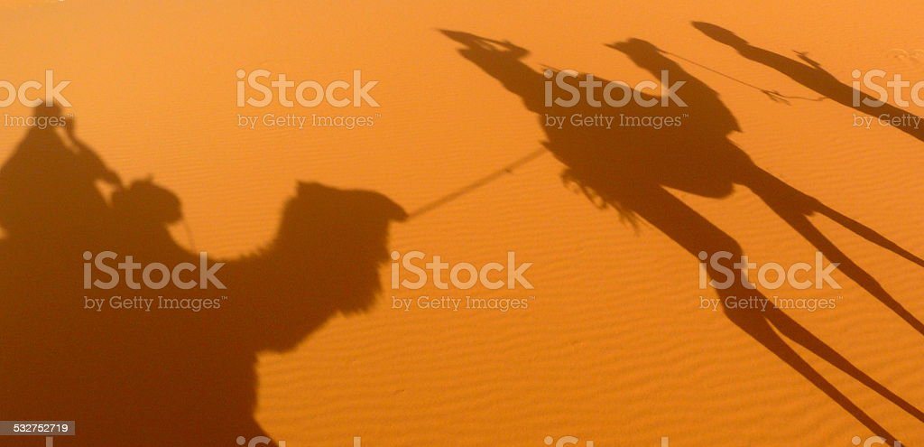 Two camel shadows projected over the desert dunes stock photo