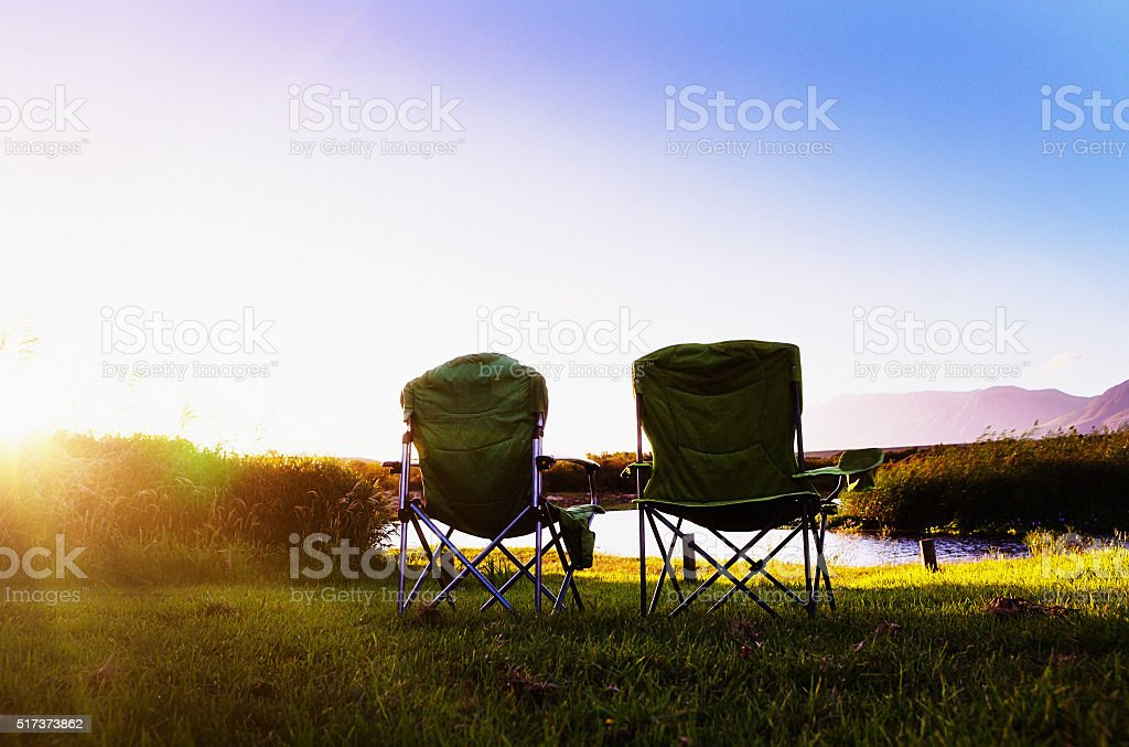 Two camping chairs by sunlit river at dusk. Idyllic. stock photo