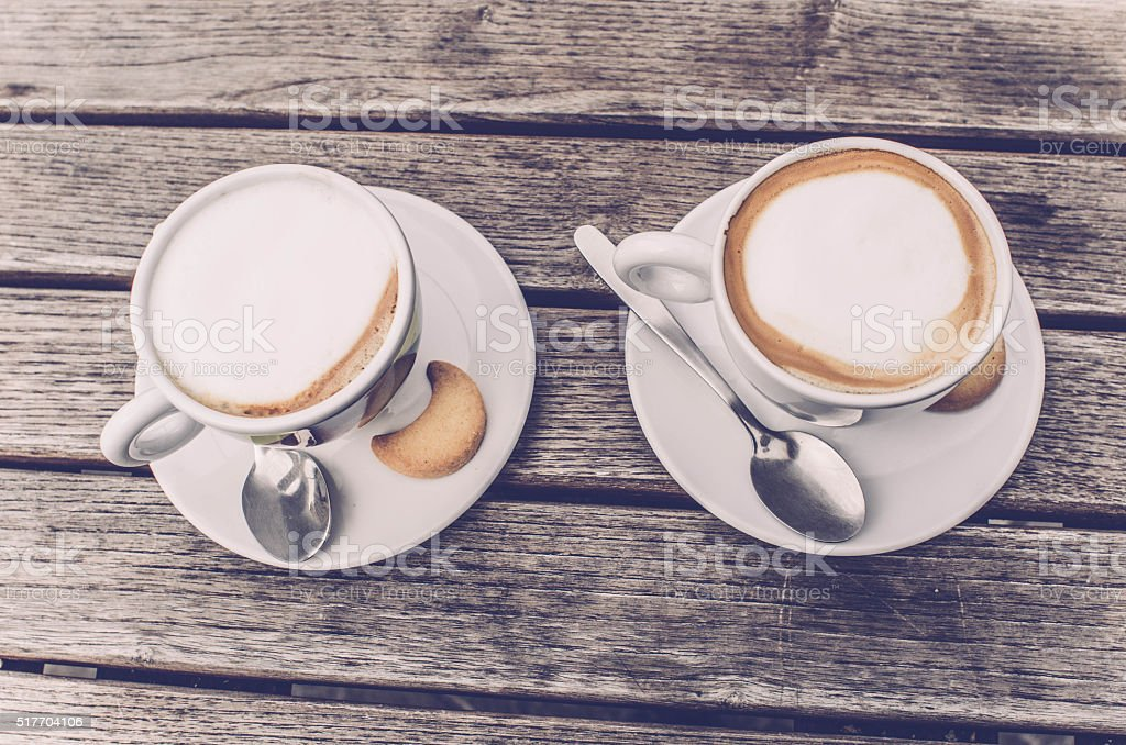 Two Cappuccino Coffee cups top view on wooden table, Italy stock photo