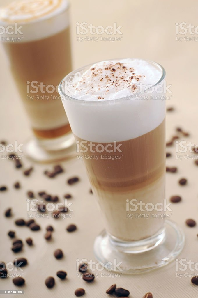 Two cappuccinos surrounded by coffee beans on a table royalty-free stock photo