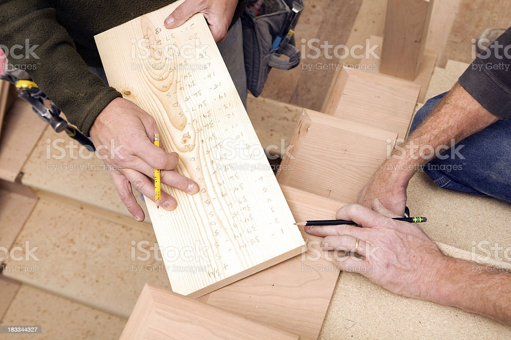 Two Carpenters Review Measurements for Stair Railing Spindles stock photo