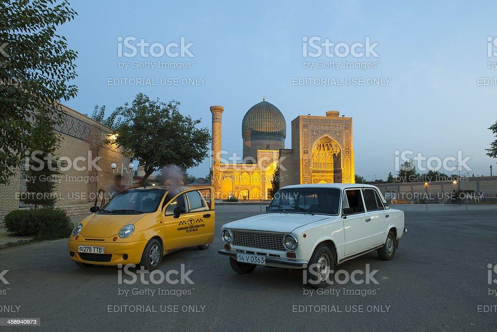 Two cars in front of Guri Amir Mausoleum, Samarkand, Uzbekistan stock photo