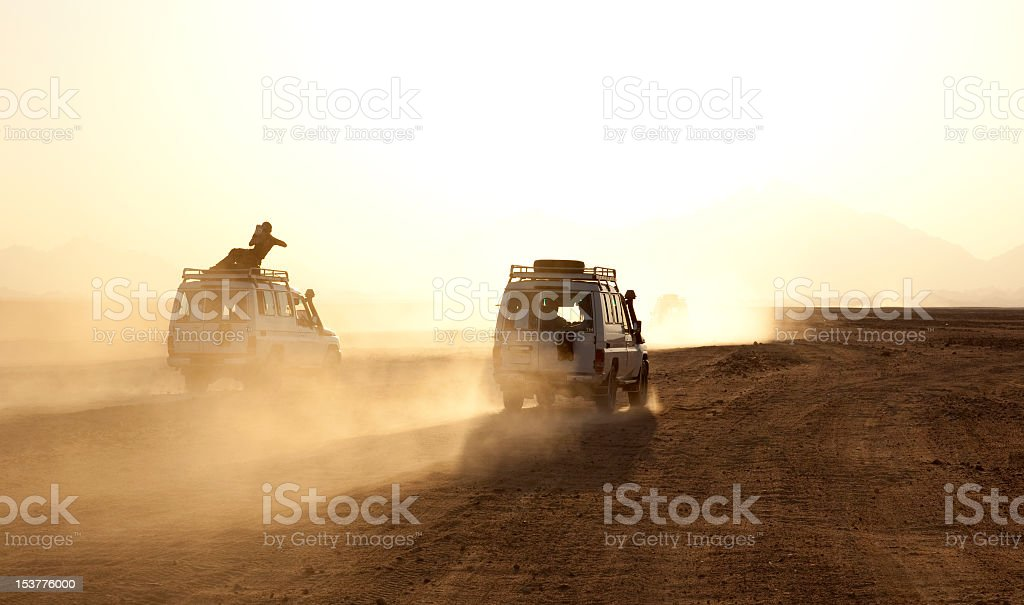 Two cars kicking up dust on a desert safari stock photo