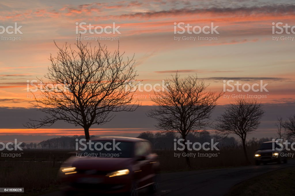 Two cars on country road with back lit trees under romantic sky stock photo